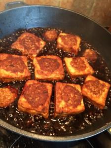 Tofu cubes simmering in sauce